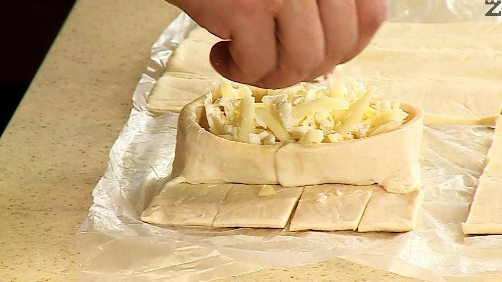 Сиренето се смесва с настърган кашкавал. В редата на всеки лист тесто се слага от плънката.