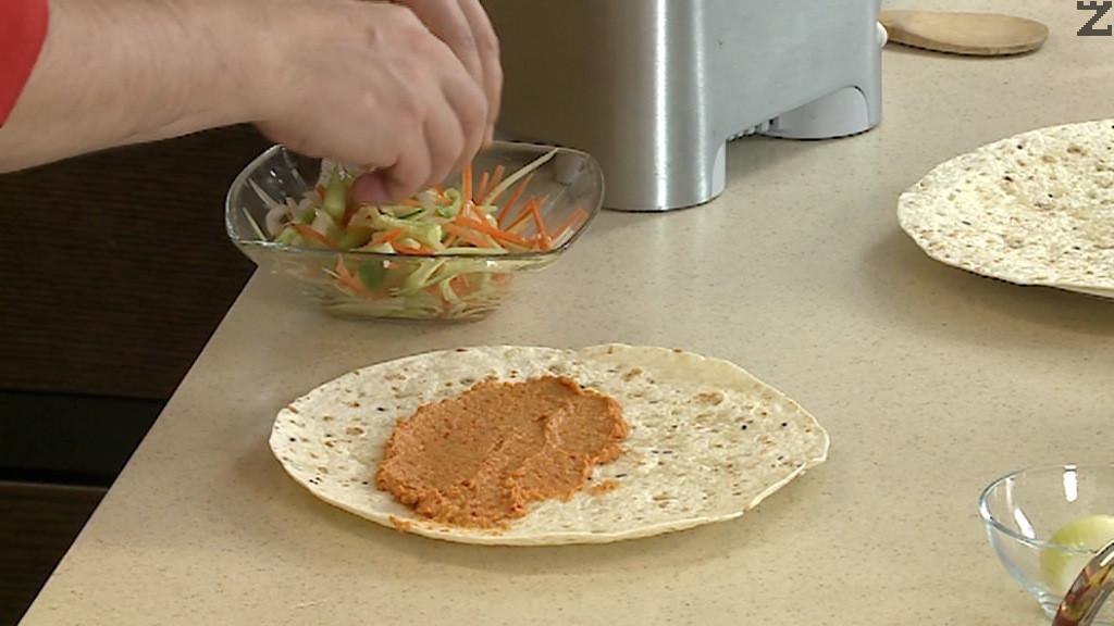 Върху тортила се слагат две супени лъжици от хумуса с чушки.