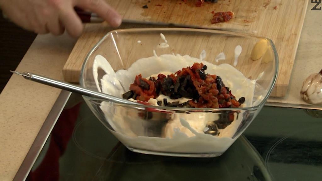 Чушките се кълцат на дребно, както и маслините, а чесъна се счуква. Сметаната се смесва пасираните яйца и сирене, добавят се чушките и добре се разбъркват.
