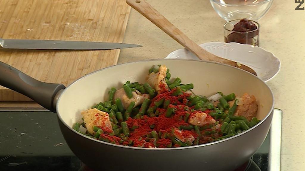 Лука се нарязва на дребно и запържва за половин минута в загрято олио. Добавя се пилешкото и след минута зеления фасул, доматено пюре, смлени домати и сол.