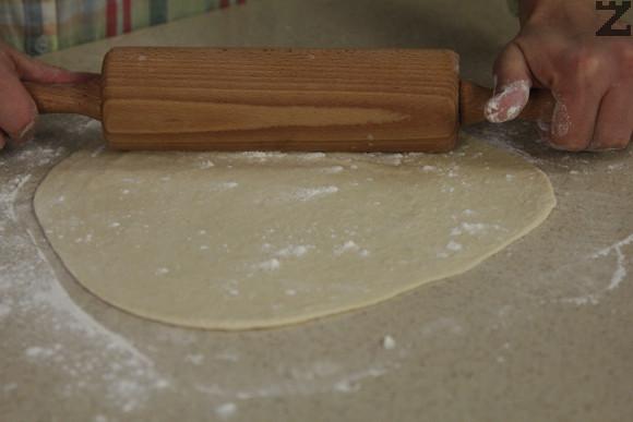 Разбъркват се. Постепенно се слагат при брашното и се омесва тесто. Оставя се да почине за 10 минути. Разделя се на четири. Всяка част тесто се разточва на кора по-голяма от тавата за печене ( 30 см ).