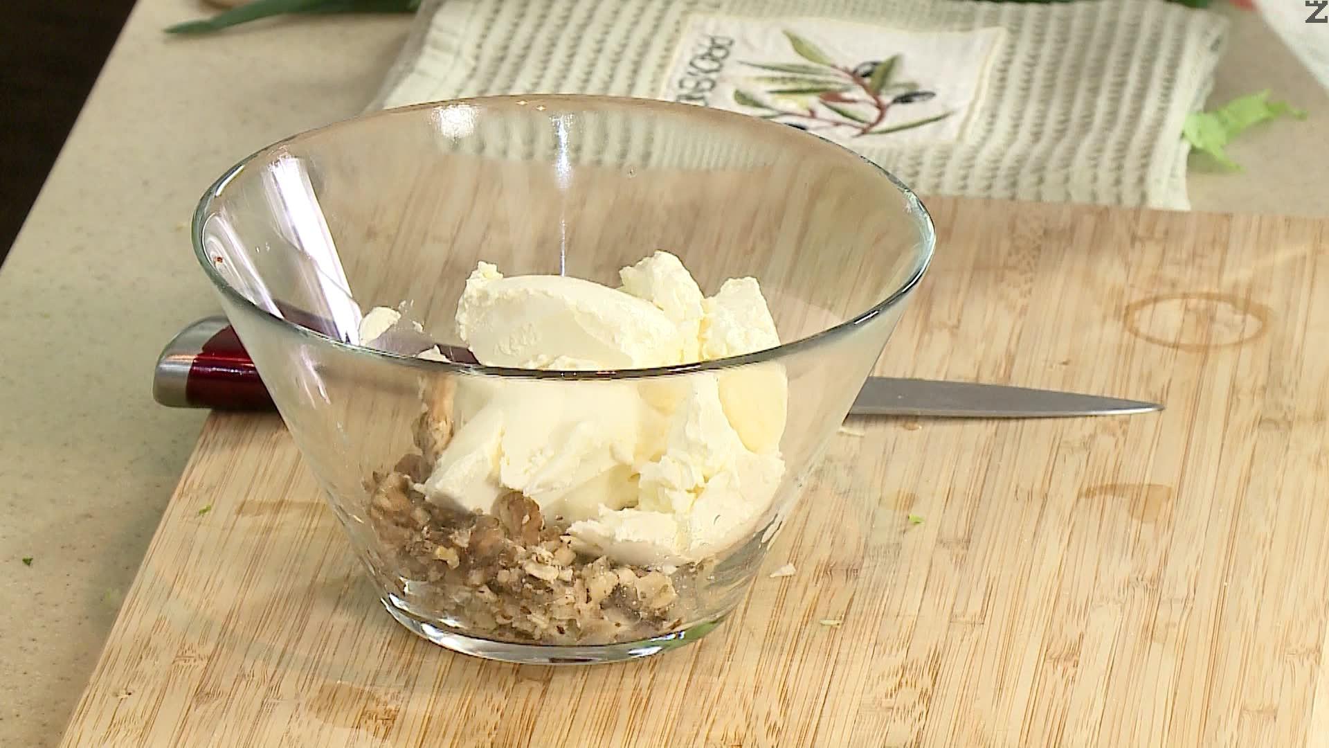 Орехите се запичат за минута в сух тиган на умерен огън. Счукват се в хаванче. Смесват се в купа заедно с крема сирене и фино нарязани две пера от пресния лук. Обърква се и с намаслени ръце се правят топчета.