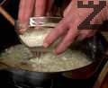 Нарязваме 1 картоф на дребни кубчета. В тигана при лука добавяме ориз и запържваме за 2-3 мин., докато стане стъклен.