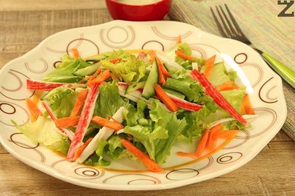 Ролцата раци, морковите и краставицата се режат на ивички, зелената салата се накъсва на дребно. Аранжират се в чиния.