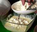 В купа счупваме и разбиваме 4 яйца. Добавяме кисело мляко и разбъркваме. Прибавяме сирене, разбъркваме и поръсваме със сода. Намасляваме тавата за печене на баница.