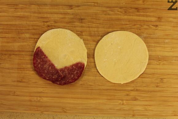 От останалите парчета се разточват малки питки около 8 см. Върху всяка питка по средата се слагат две-три филии тънко нарязан салам.