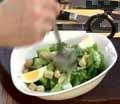 Гарнираме салатата с нарязани на осминки обелени яйца, поръсваме с кротони и нанасяме малко от соса. С останалото количество сос доовкусяваме салатата.