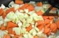 Запържваме в олио нарязан на ситно лук, след 30 сек. добавяме морков. Прибавяме нарязан на ситно селъри. Разбъркваме и запържваме 2 мин.