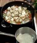 Изпичаме брашно на сух тиган до златисто. Нарязваме печурките на едро и ги прибавяме към останалите зеленчуци. Пържим още 5 мин. и разбъркваме периодично.