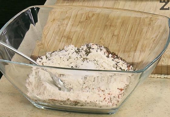В тавичка се смесва брашно, босилек, риган, червен пипер, чесън на прах и 1 ч.л. сол.
