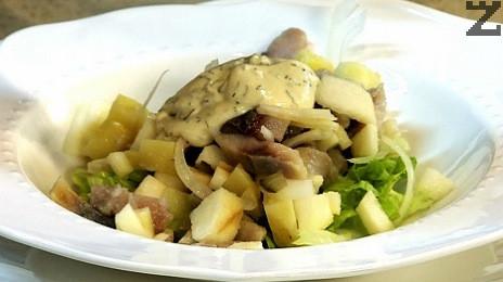 В чиния се слага зелена салата, сместа с картофи и ябълка, филе херинга и дресинг.
