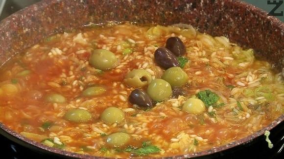 Задушаването продължава докато ориза поеме течноста. Слагат се накрая маслини задушават се за минута, две и ястието е готово.