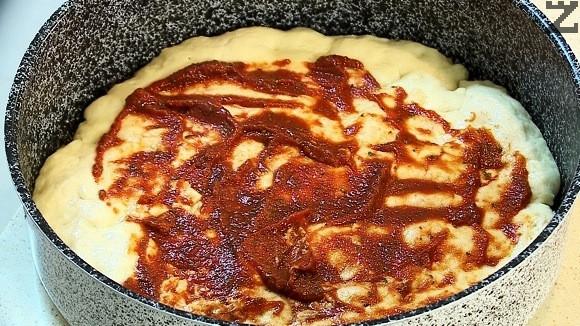 Върху запечения блат за пица се нанася сос, и покрива половината настърган на едро ренде кашкавал, нарязан на парчета бекон и останалата половина кашкавал.