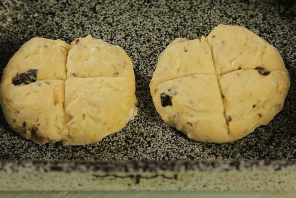 От него се оформят питки с тегло 100 грама, сплескват се и нареждат в тава. В угрибка или нож се прави кръст и питките се намазват с мляко.