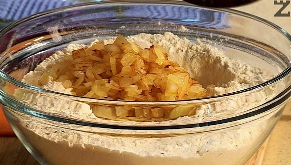 В купа се пресява брашното, добавя се бакпулвер, посолява се, слага се мащерка и се разбърква. Оформя се кладенче и се слага карамелизирания лук, налива се зехтин и 200 мл вода вода.
