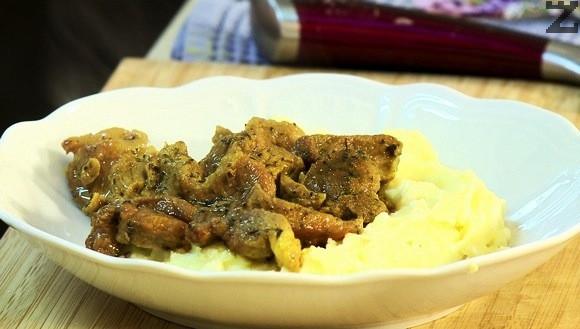 Картофеното пюре се слага в чиния и отгоре се подреждат задушените късчета свинско месо.