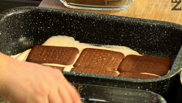 Покрива се с потопени в прясно мляко бисквити. Слага се крем, бисквити с мляко, крем, бисквити и последния пласт е от крем.