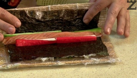 Върху непокритата с ориз кора се реди сьомга и краставица. Навива се руло и реже на осем.