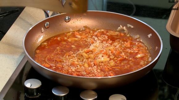 """Оризът се измива много добре и отцежда. Слага се в тигана и запържва за половин минута като се разбърква докато стане """"стъклен"""". Поръсва се с червен пипер разбъкрва се и залива с 250 мл гореща вода."""