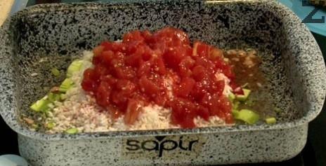 Запечените кюфтенца се изваждат от тавата и в нея се слага ориз, скълцани на дребно домати, босилек, магданоз, сол и праз.