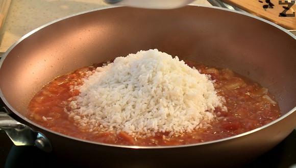 Оризът се измива много добре и слага в тигана. След половин минута запържване се залива с 200 мл топла вода. На тих огън се оставя да се задуши.