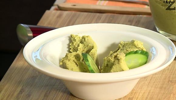 Хумуса се слага в чиния и гарнира с резени краставица.