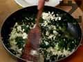 Поръсваме спанака със суха зеленчукова подправка и черен пипер, натрошаваме краве сирене и разбъркваме.