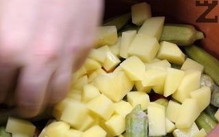 Картофите се обелват и режат на кубчета. Слагат се в гювеча.