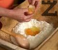 Правим кладенче в брашното, разбиваме 4 яйца, като на едното отделяме жълтъка за намазване. Добавяме 5 с.л. захар и разбъркваме.
