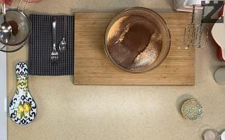 Брашното заедно с какаото се пресяват върху яйцата. Внимателно се разбъркват за кратко.