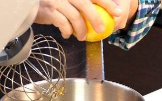 Налива се затоплено мляко, олио ванилова захар. Лимоновата кора се настъргва на фино ренде. Добавя се сол и половината от разтопеното масло. Разбъркват се за кратко.