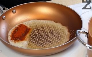 В тиган се загрява масло, поръсва се с червен пипер и след 3-4 секунди се залива с два черпака от супата.