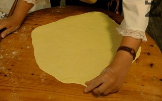 Всяка голяма топка се разточва на тънка кора с размер около 30-40 см. ( малко по-голям от тавата за печене ) Разтопява се масло за намазване и смесва с олио.