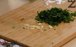 Нарязва се на дребно чесън и магданоз. Прибавят се при чушките и се размесват.