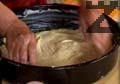 Потапяме топките тесто в тенджерата с мас и ги разтегляме с ръце, докато получим кори, които подреждаме в тавата. Натрошаваме сирене и покриваме с кори.