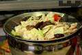 В голяма купа поставяме цедка и изсипваме пилешкото и зеленчуците, за да се отцеди мазнината.