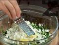 Прибавяме нарязан пресен лук и натрошено сирене. Накисваме сварените яйца в студена вода за 1-2 мин. и ги обелваме. Настъргваме 2 яйца в купата със салата.