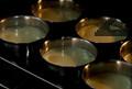 Слагаме тавичката във фурна и сипваме студена вода, която да стига до средата на чашките. Печем във фурна, загрята на 150-160 градуса, около 60-90 мин. Сервираме крем-карамела охладен, обърнат в чинийка.