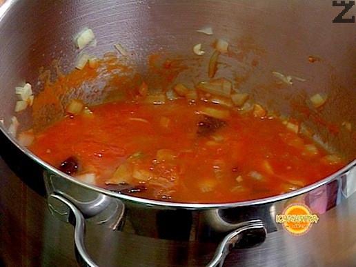Продължаваме запържването за още една минута и слагаме пасирани домати . Налива се 200мл топла вода, за да се получи средно гъст сос и се прибавя захарта и сол на вкус. Вари се 10 минути на тих огън под капак.