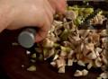 Нарязваме печурки, кисели краставички и пресен лук на ситно. Прехвърляме половината картофи в тавичка и ги нанасяме равномерно.