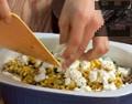 Натрошаваме в тавичката сирене и намазваме цялата повърхност с цедено кисело мляко. Покриваме с останалото количество картофи и поръсваме с настърган кашкавал.