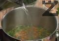 Наливаме 1-1,5 л гореща вода, добавяме сол, ориз и попарена коприва. Варим под капак около 20 мин. на слаб огън. На десетата минута от варенето прибавяме консервирани домати.