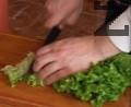 Нарязваме зелена салата на ивички и я прехвърляме в купа със сварени и охладени със студена вода спагети. Нарязваме пресен лук и чесън.