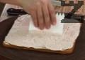 Намазваме охладения изпечен сладкиш с крема. Набраздяваме повърхността със сладкарски гребен и нарязваме сладкиша на квадратчета.