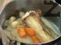 Слагаме шкембето в тенджера със студена вода. Добавяме запечения кокал и зеленчуците.