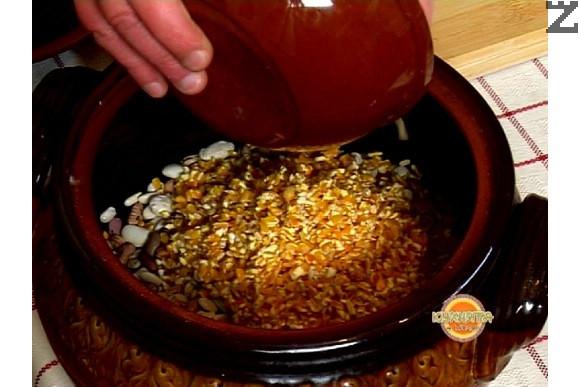 Прехвърляме фасула в глинен гювеч, прибавяме счукана царевица, кромид лук и морков, нарязани на ситно. Добавяме олио и поръсваме с червен пипер.