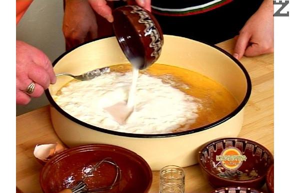 В друга купа се слага киселото мляко, прибавяме сода бикарбонат и оцет. Разбъркваме и изсипваме сместа в купата с яйцата, прясното мляко и мая и хубаво разбъркваме.