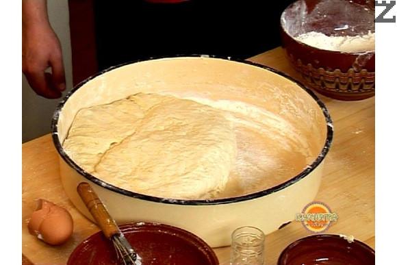 Сместа се слага в голяма тава и постепено се прибавя брашното. Замесва се меко тесто и когато е готово го намазваме с олио, Оставяме да бухне (втаса) за 1-2 часа на топло място.