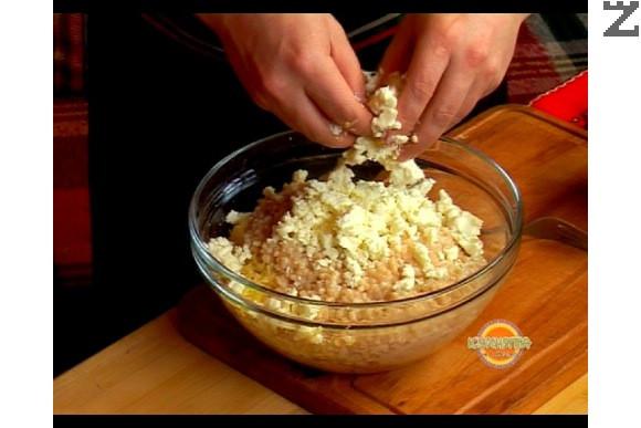 В купа настъргваме обелените картофи на едро ренде. Прехвърляме кускуса при картофите, натрошаваме сиренето и добавяме яйца.