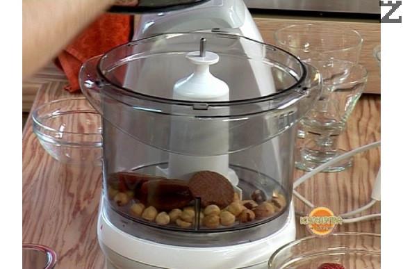 В кухненски робот се мелят на фини трохи лешници и какаови бисквити. Постепенно добавяме пчелен мед и продължаваме да смиламе за 30 секунди до получаване на лепкава смес.